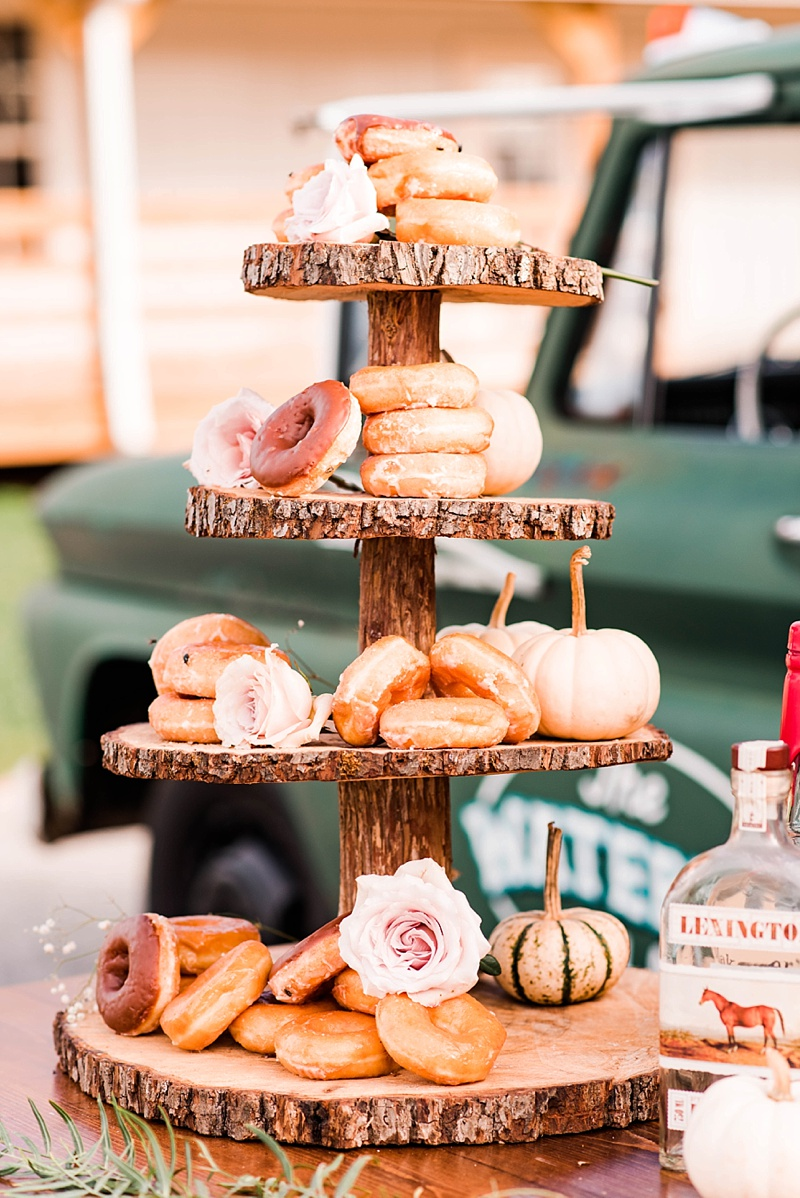 Rustic donut stand made out of tree slices and stumps for outdoor barn wedding