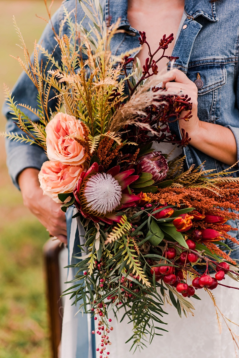 Gorgeous fall wedding bouquet with red king protea and wild greenery
