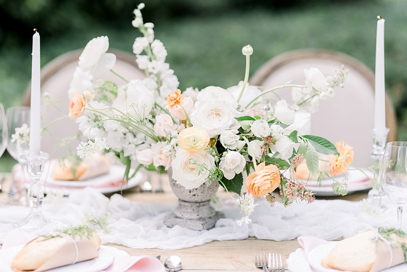 Pastel asymmetrical wedding centerpiece with ranunculus and roses