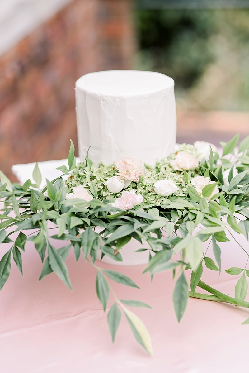 Small one tier white wedding cake with overflowing greenery