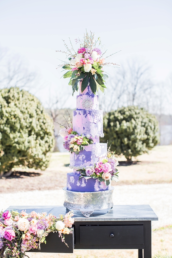 Modern garden glam purple and pink wedding cake with towering roses and greenery