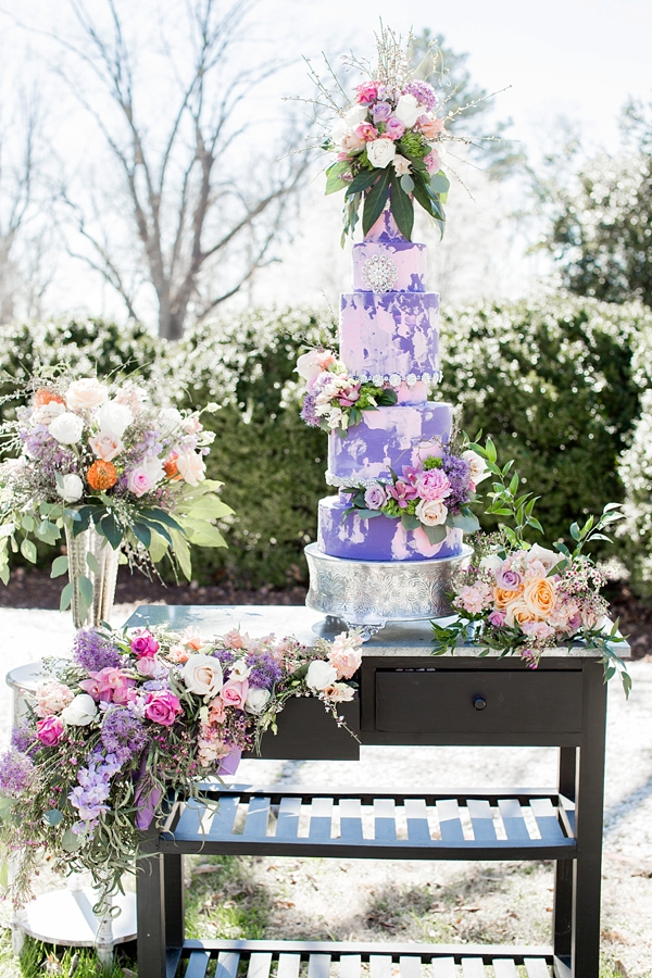 Epic 5 tiered purple wedding cake with painterly pink details and garden flowers
