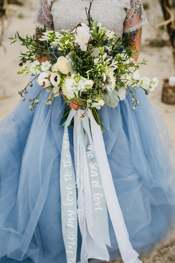Wild organic indie beach wedding bouquet with long blue ribbons and white calligraphy