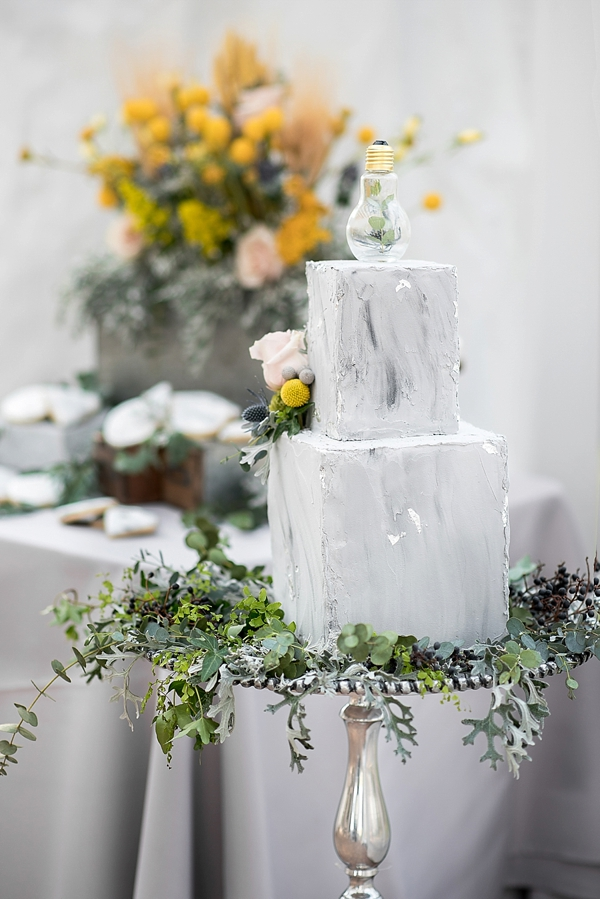 Industrial concrete inspired wedding cake with glass light bulb cake topper