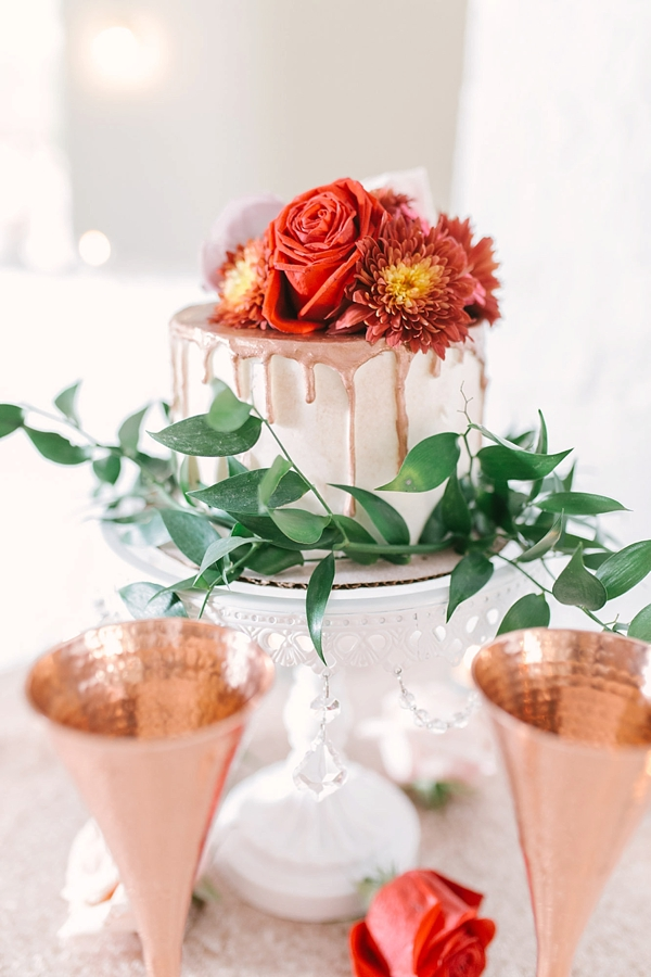 Mini wedding cake with copper drip frosting and bright red orange flowers