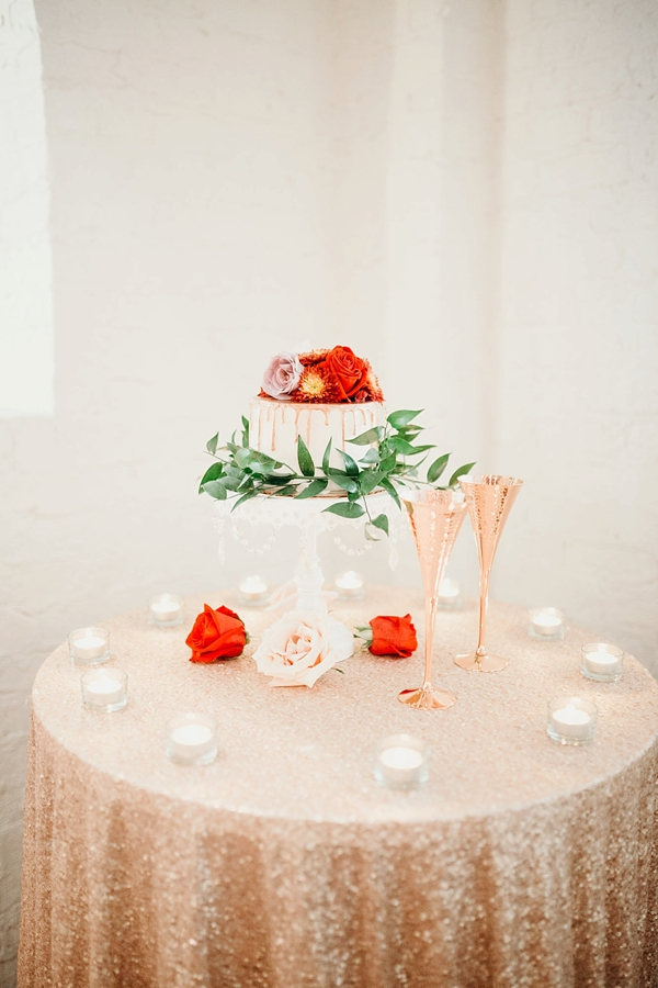 Wedding cake table with gold sequin tablecloth and copper toasting glasses
