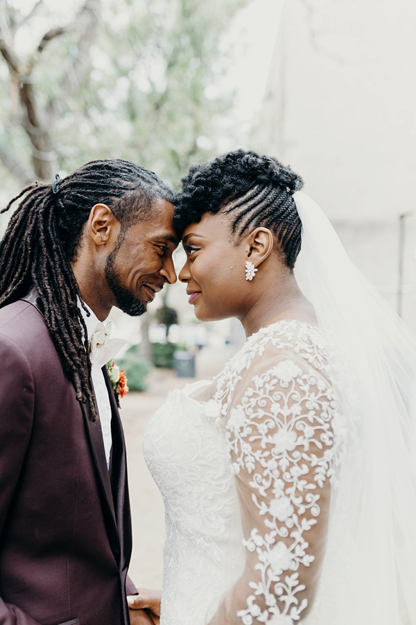 Stylish black bride and groom with custom wedding suit and dress