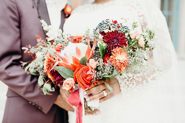 Orange and red modern wedding bouquet with proteas and dahlias