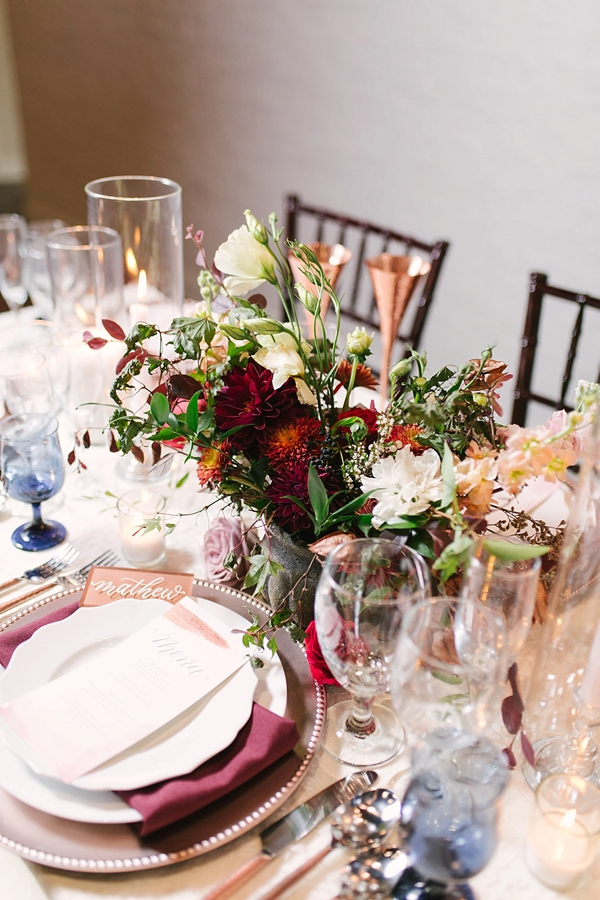 Burgundy red and orange flowers in concrete vase surrounded by copper wedding toasting glasses