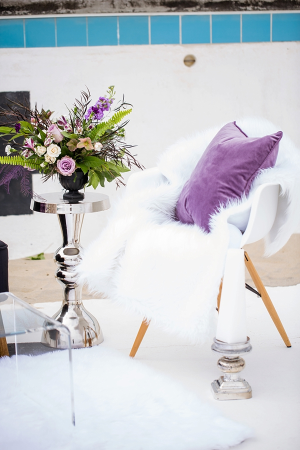 White chair with purple pillow and faux fur throw for modern contemporary wedding seating area