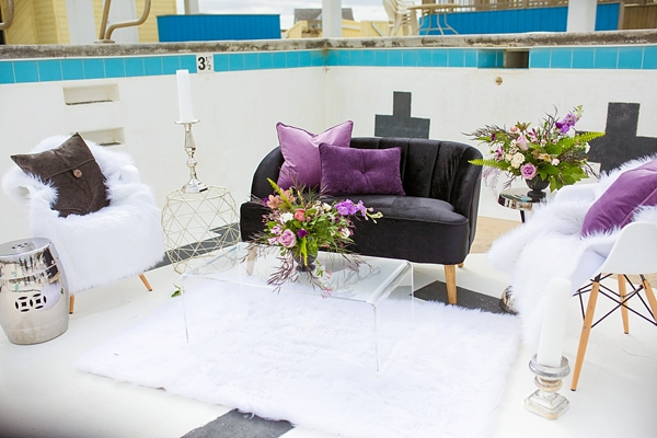 Modern purple and black wedding lounge setup with acrylic table and geometric chairs