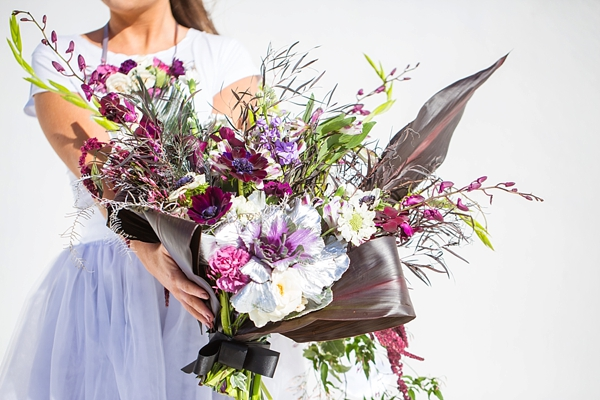 Asymmetrical modern tropical wedding bouquet with purple and green with pops of metallic silver painted ornamental cabbage
