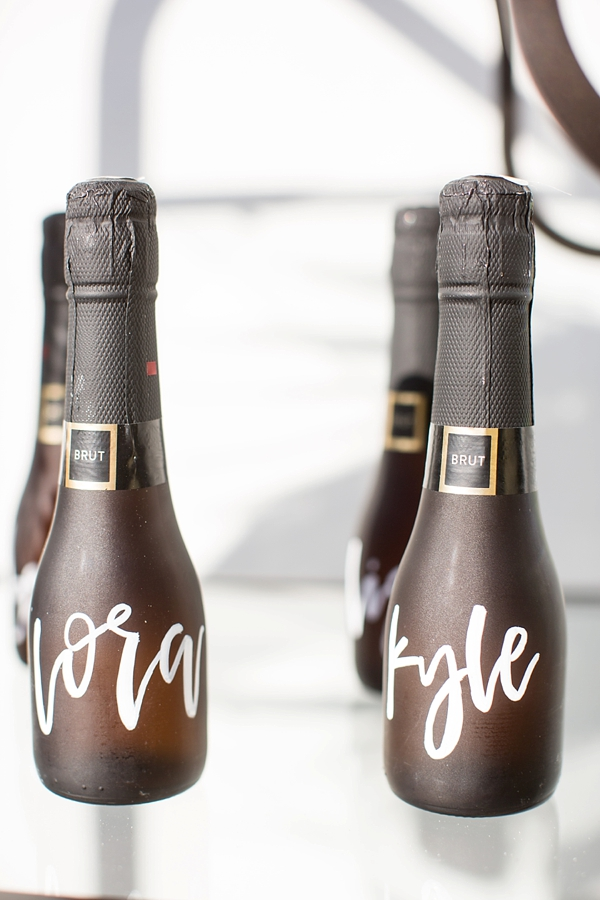 Handlettered mini champagne bottles for wedding place cards