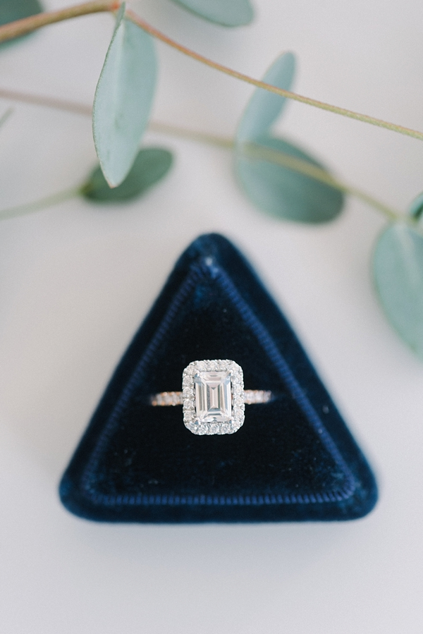 Emerald cut diamond engagement ring with navy blue triangle velvet ring box