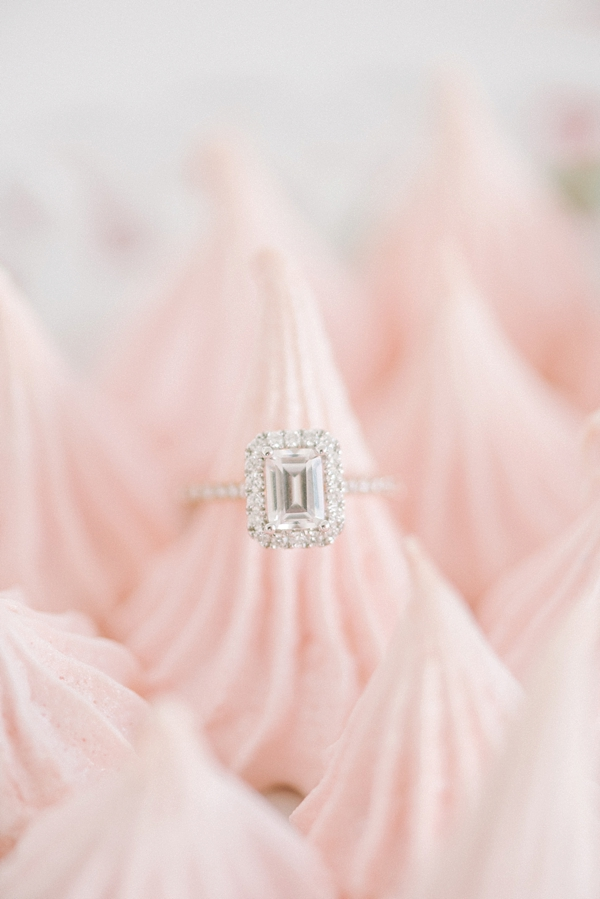 Emerald cut diamond engagement ring with delicate diamond encrusted band on pink raspberry meringues