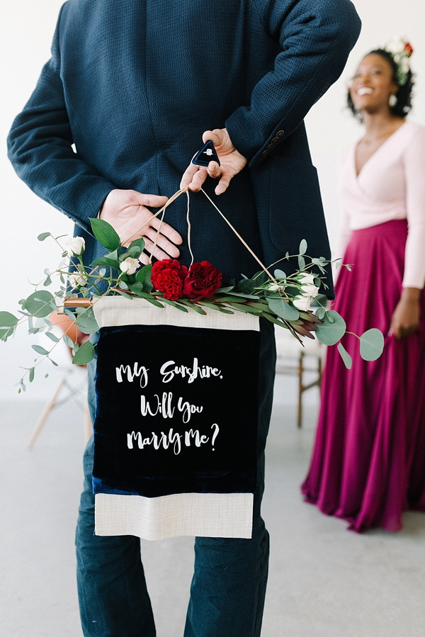 DIY velvet marriage proposal banner with floral swag