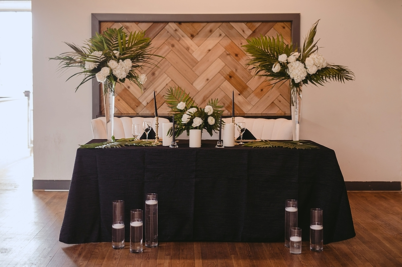 White black and gold wedding sweetheart table for chic modern tropical reception look