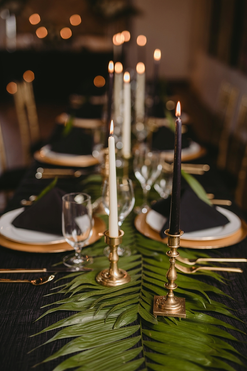 Black and white candlesticks with gold flatware for a modern tropical wedding reception