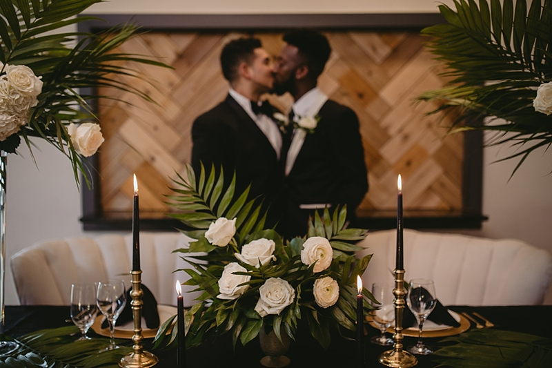 Modern tropical wedding sweetheart table with palm leaves and black candles