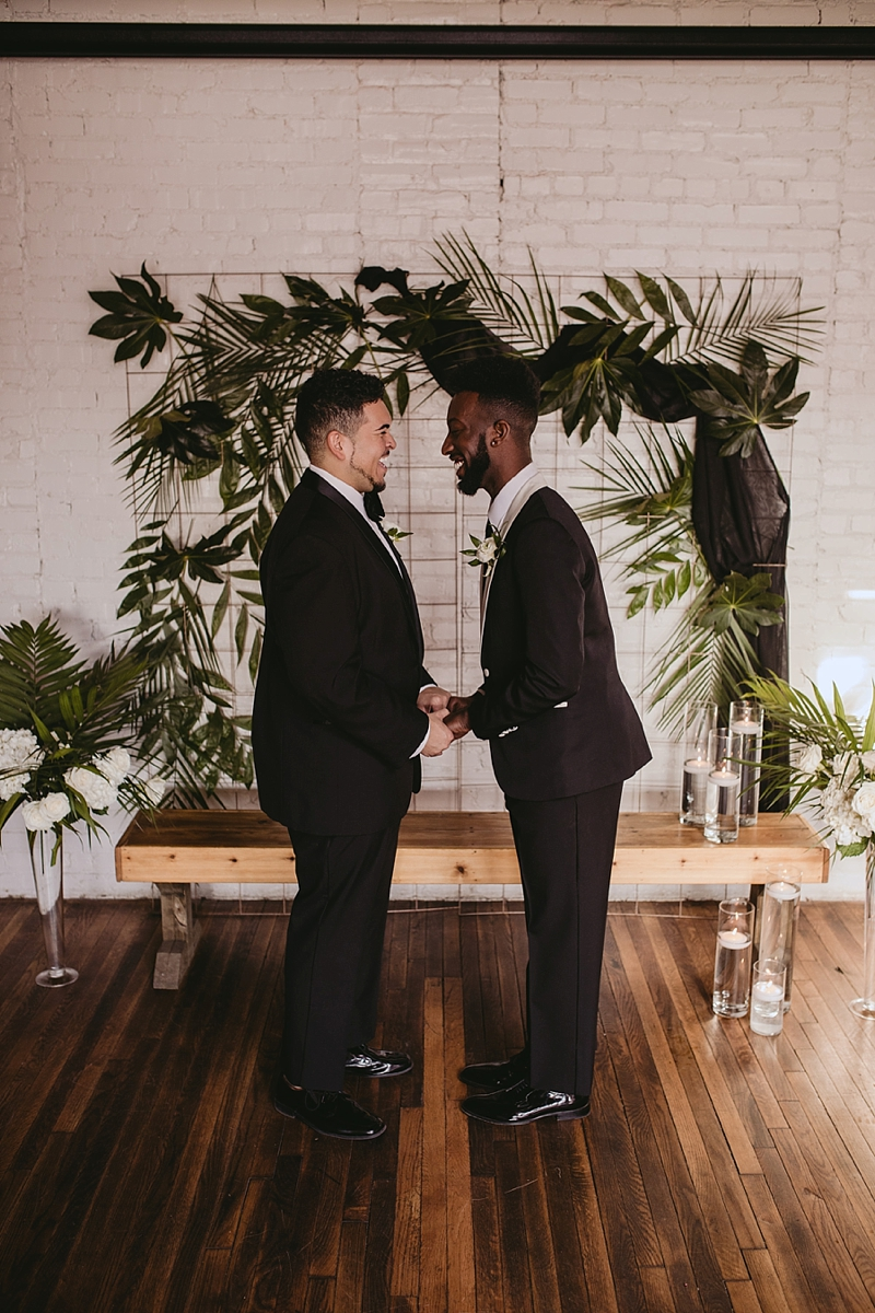 Gorgeous wedding ceremony with two grooms and gold grid backdrop with tropical greenery at the Hof building in Richmond Virginia