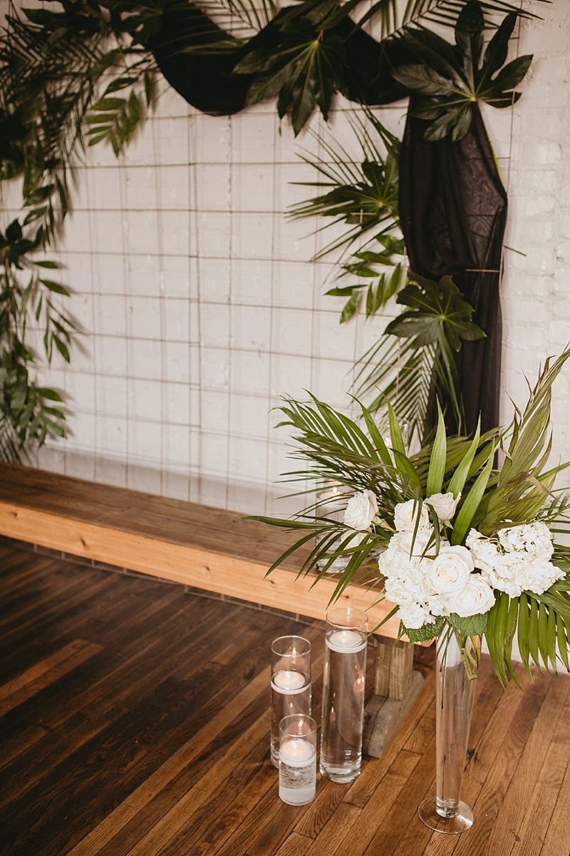 Modern tropical wedding ceremony setup with gold grid and tropical greenery and palm leaves