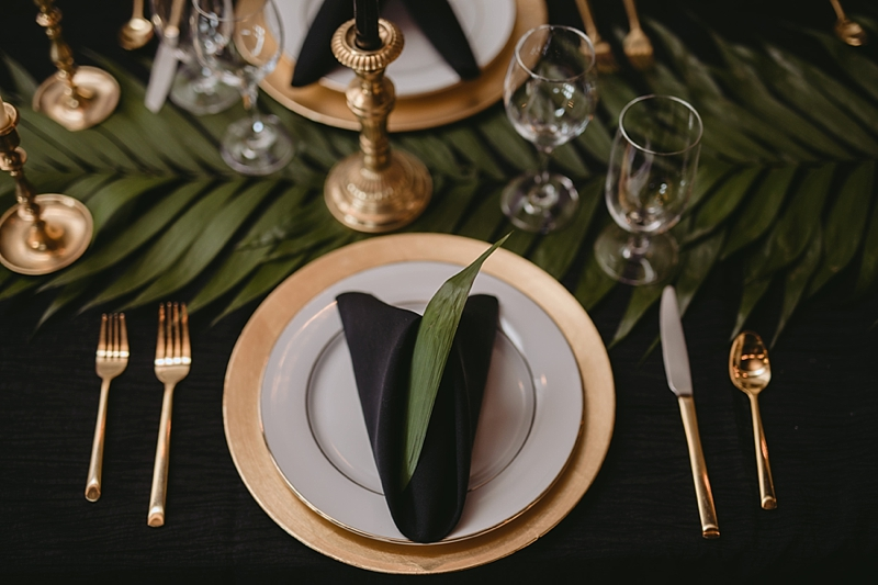 Simple gold and white table setting with black napkins for tropical wedding reception