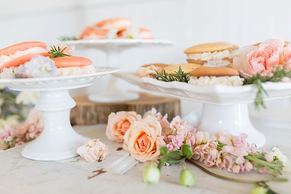 Wedding dessert bar with mini whoopie pies on vintage white cake stands