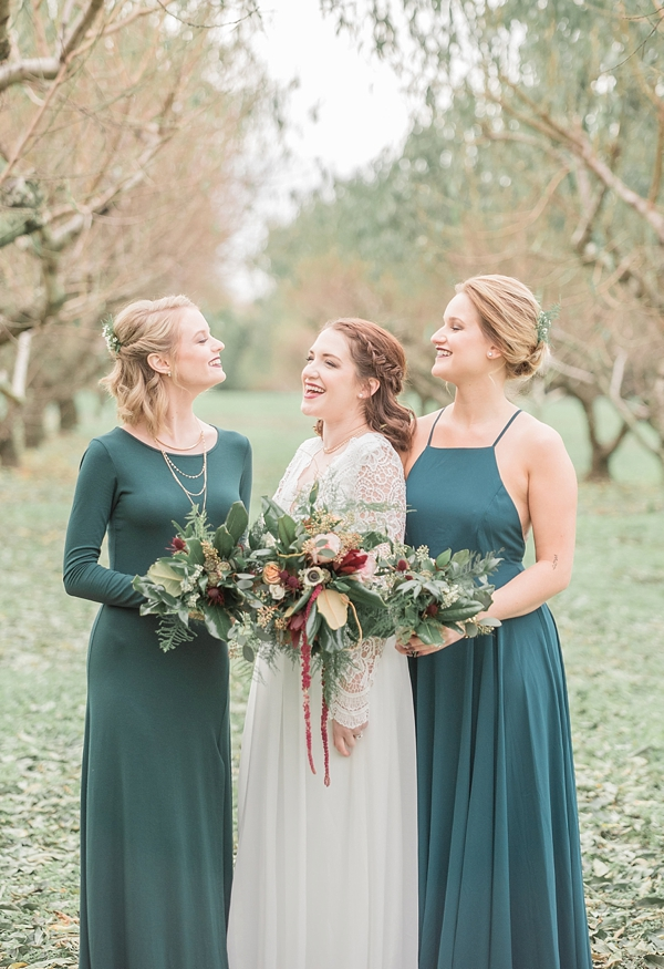 Bridesmaids in green with cranberry red bouquets for holiday wedding