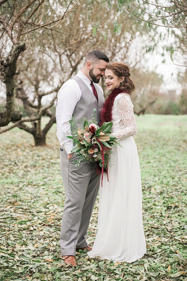 Bride with a wine colored red faux fur scarf and gorgeous lace dress