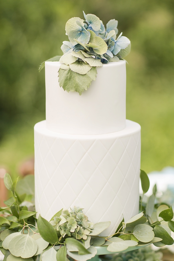 Simple quilted white wedding cake with hydrangeas