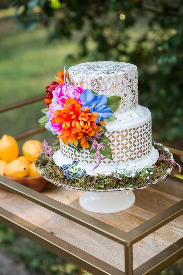 Brightly colored tropical wedding cake with modern gold design