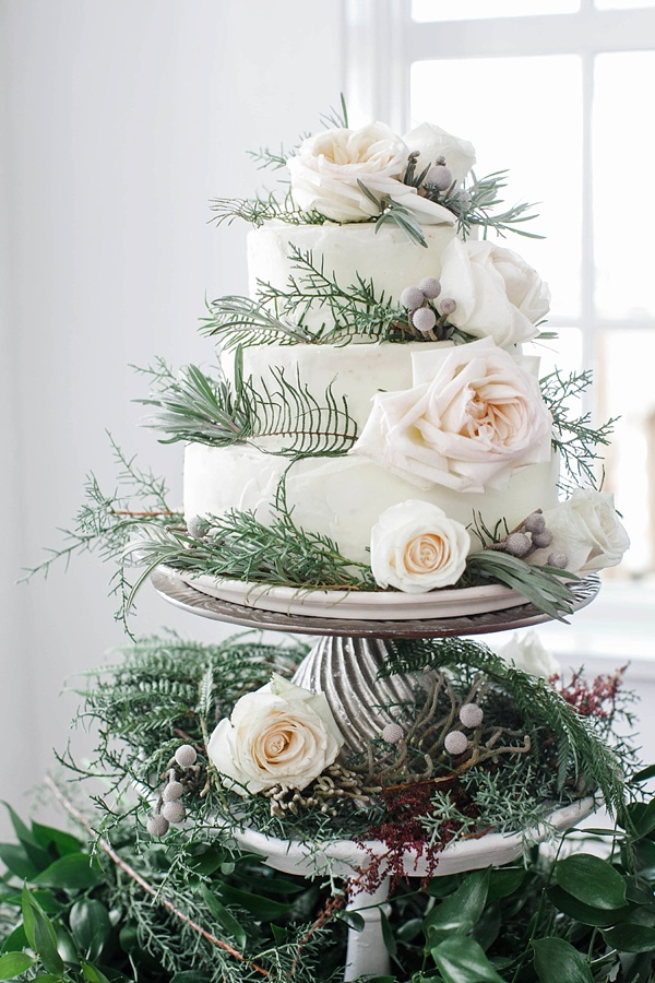 Wintry white wedding cake on tiers of vintage china and greenery