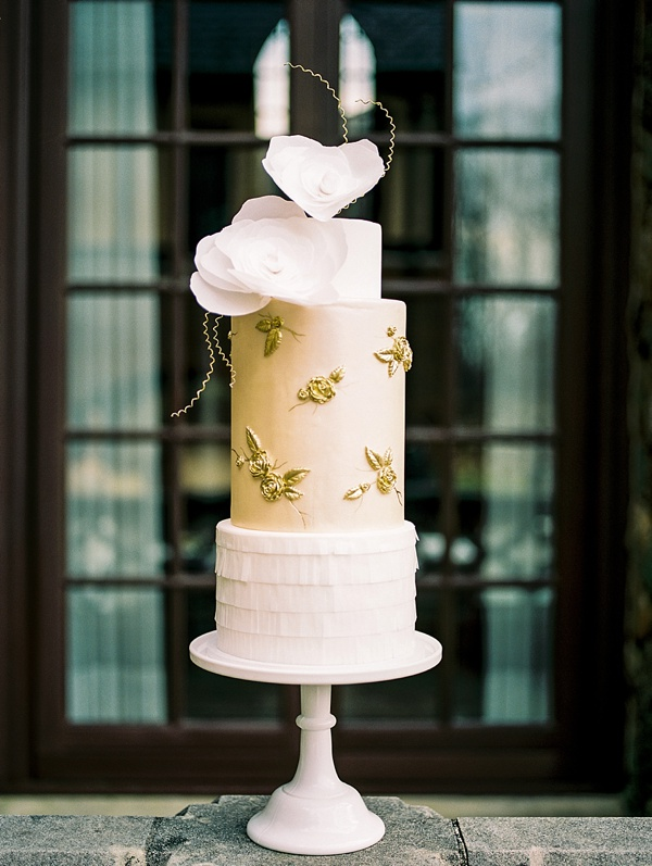 Luxe wedding cake with gold bas relief sugar roses and artistic topper