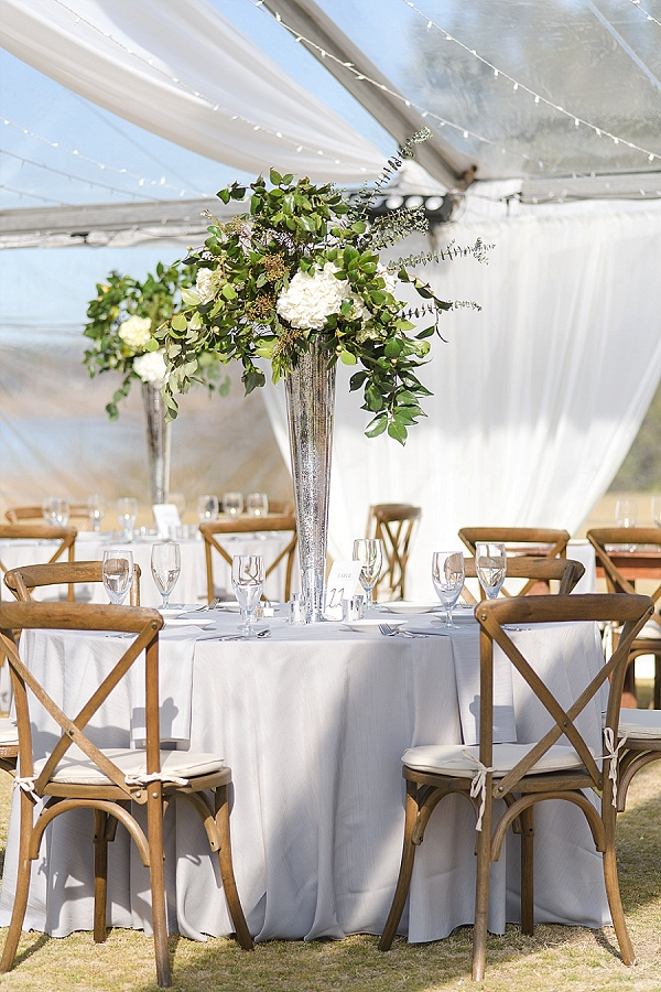 Tall wedding reception centerpiece with greenery and white hydrangea flowers
