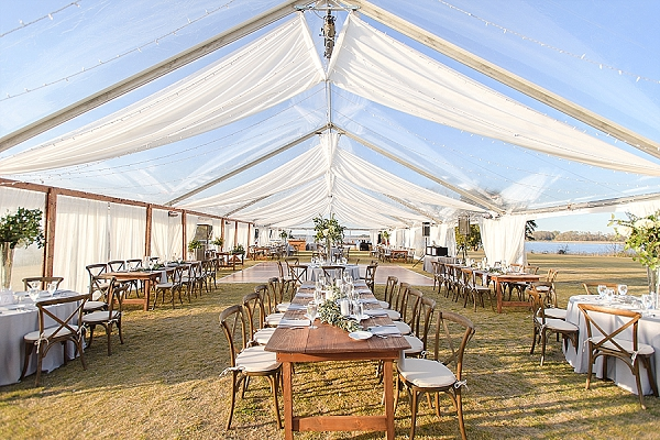 Gorgeous clear tent and bistro lights with draping for rustic outdoor wedding reception