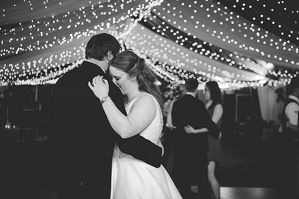 Bistro lights and romantic bride and groom dance moment