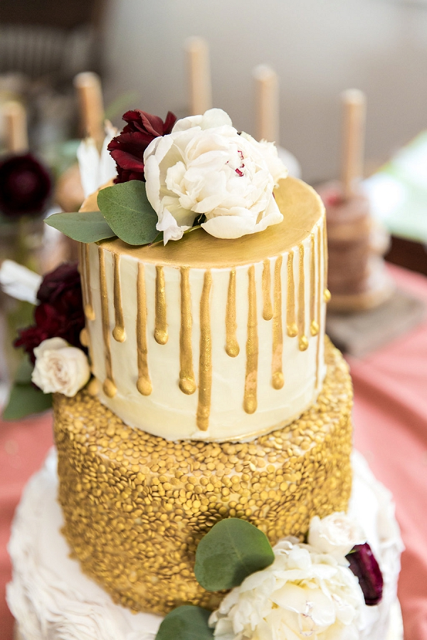 Gold and white drip wedding cake with red and white flowers