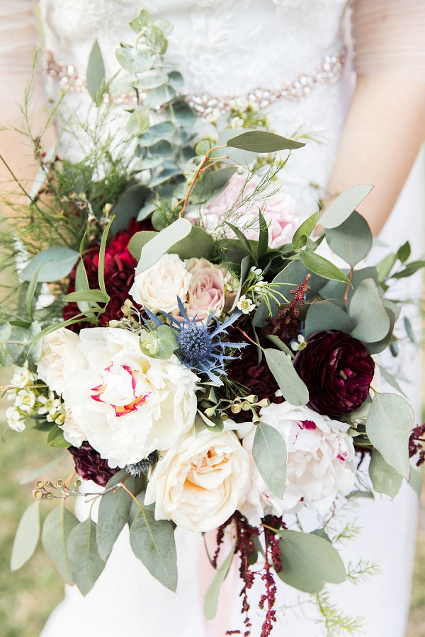 Beautiful rustic wedding bouquet with blue thistle and ranunculus