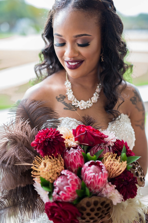 Tattooed bride with gorgeous fall inspired bouquet with ostrich feathers
