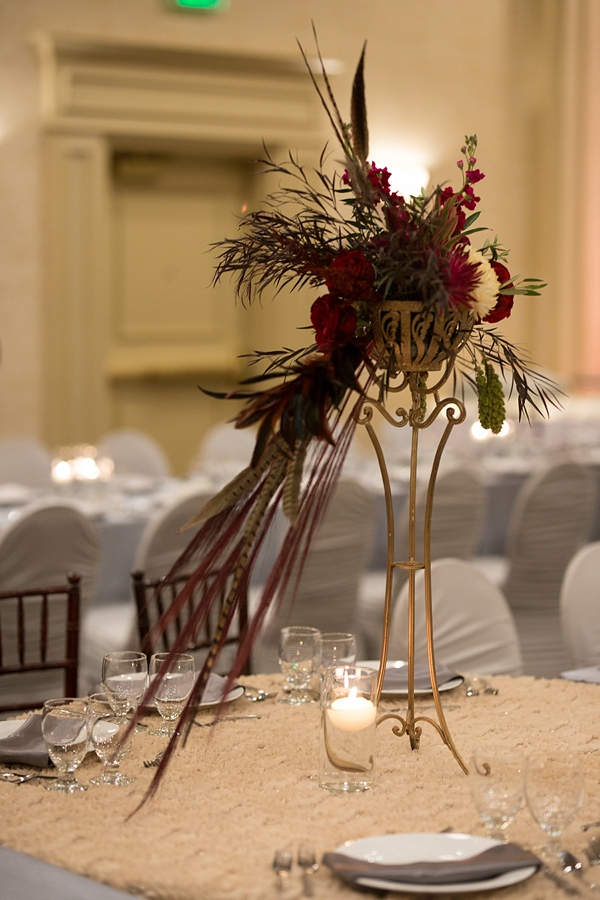 Glamorous tall wedding centerpiece with pheasant feathers