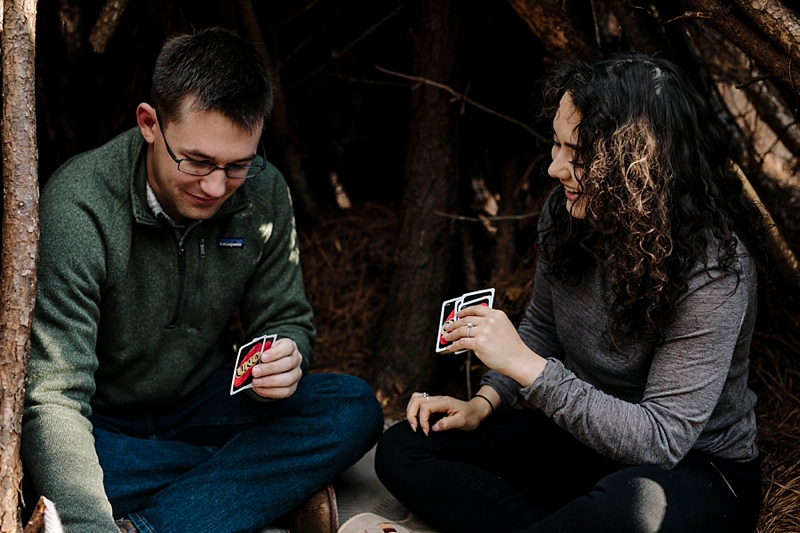 Engaged couple playing UNO cards for their woodsy engagement session