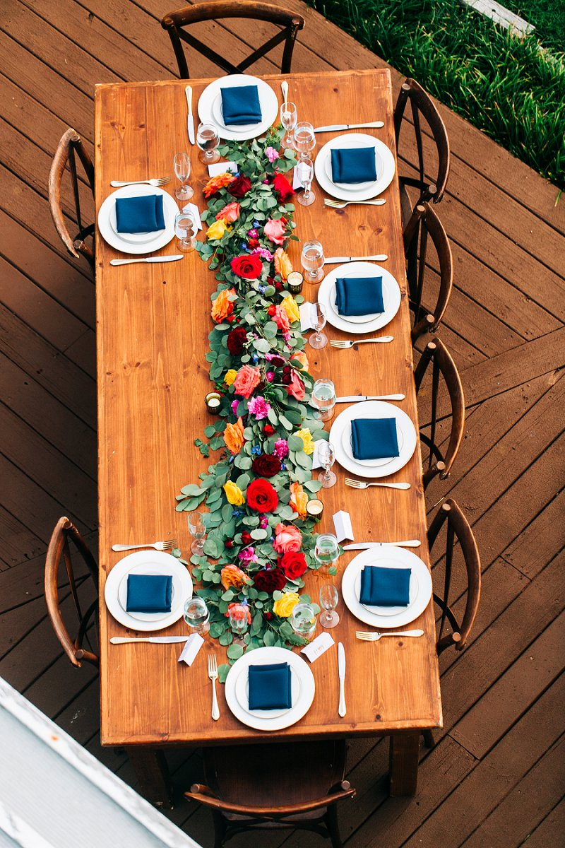 Long wooden farm table with long flower garland and navy blue napkins for an outdoor beach wedding reception dinner