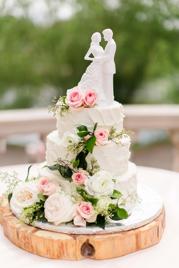Classic rustic white textured wedding cake with pink roses and greenery