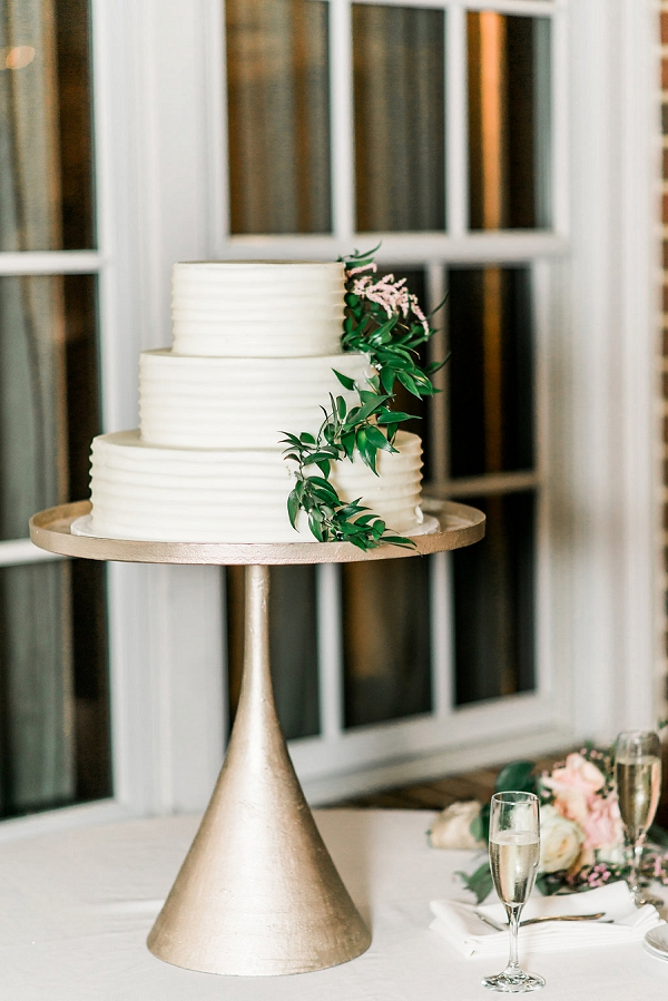 Sweet small tiered white wedding cake with simple greenery detail on a tall gold cake stand