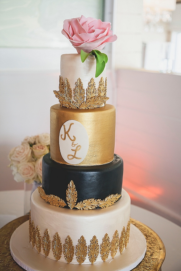 Elegant gold and black wedding cake with monogram