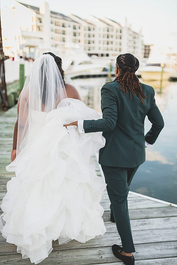 Dapper bride carrying her bride's dress train
