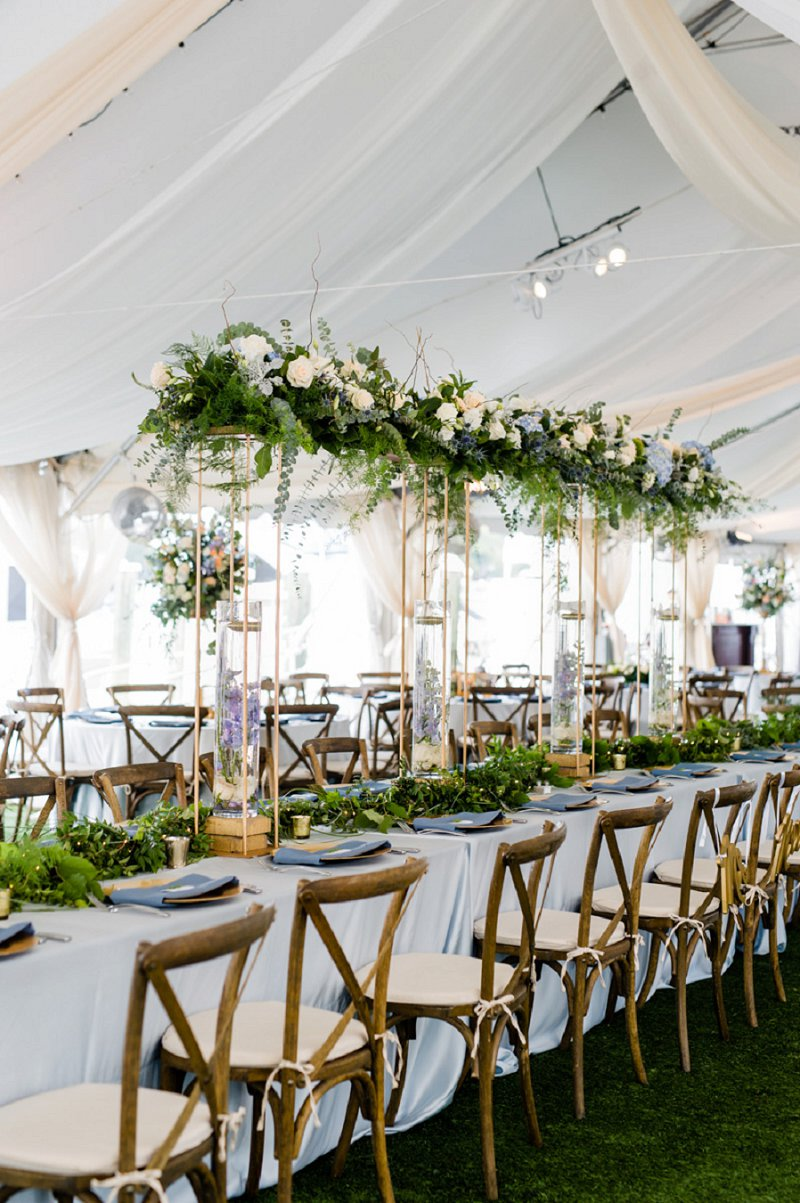 Tall and elevated wedding flower centerpieces with greenery and small flowers for a tent wedding