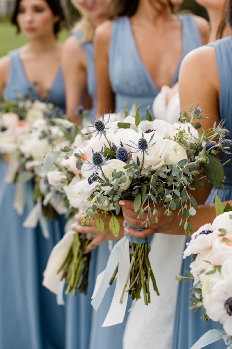White wedding bouquets held by bridesmaids dressed in blue
