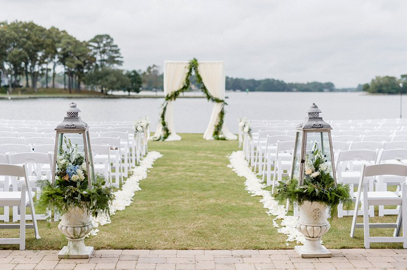 Classic wedding ceremony on the water with giant lanterns and drapery
