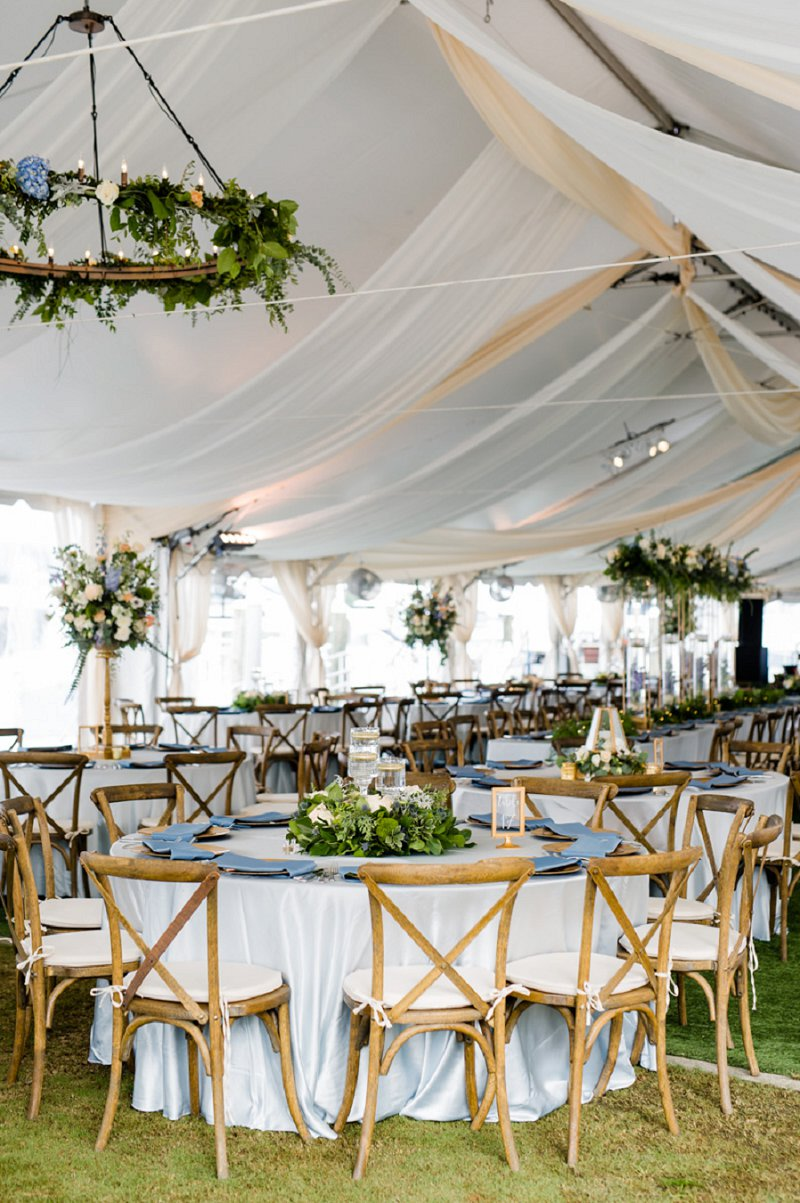 Gorgeous tented outdoor wedding reception with drapery and wooden x back chairs for classic rustic celebration